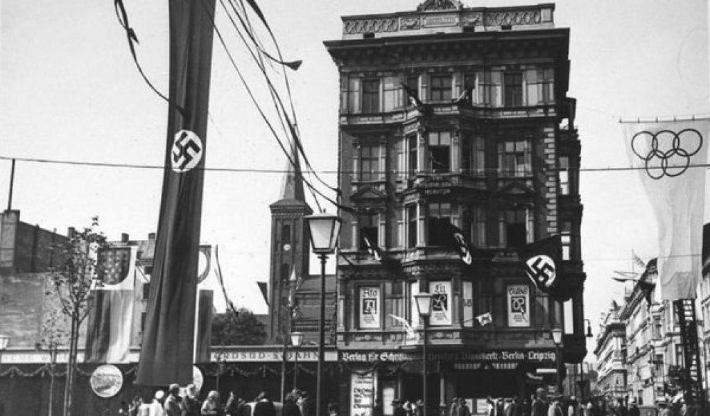 Berlin blev op til og under de olympiske sommerlege i august 1936 præget af nazistiske faner og udsmykninger. Her ses hjørnet af Unter den Linden og Neue Wilhelmstrasse den 21. juni 1936. Foto: Bundesarchiv.